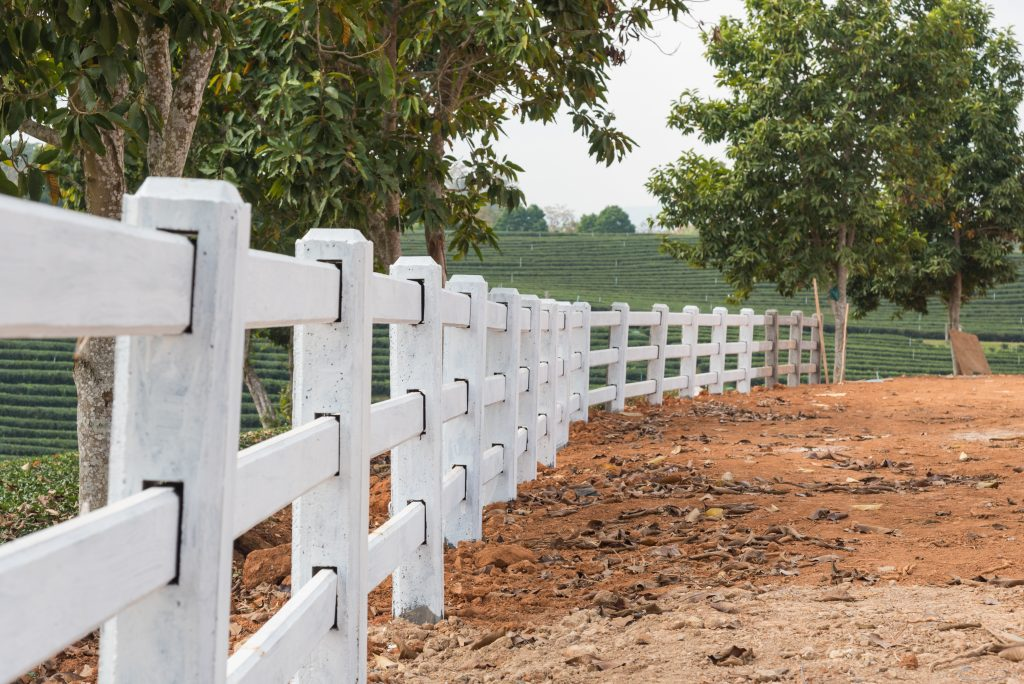 white fence installed on ground in tea plantation