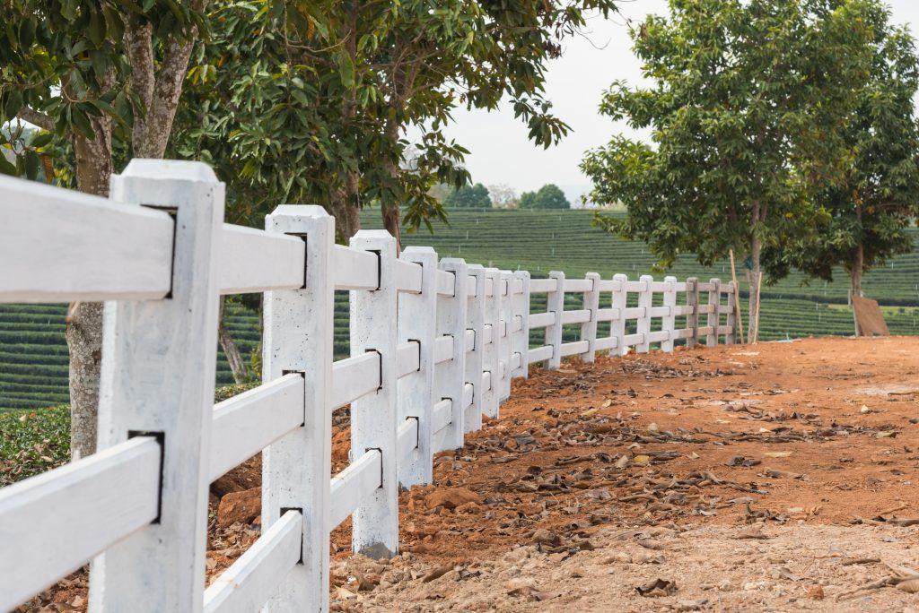 white fence installed on ground in tea plantation